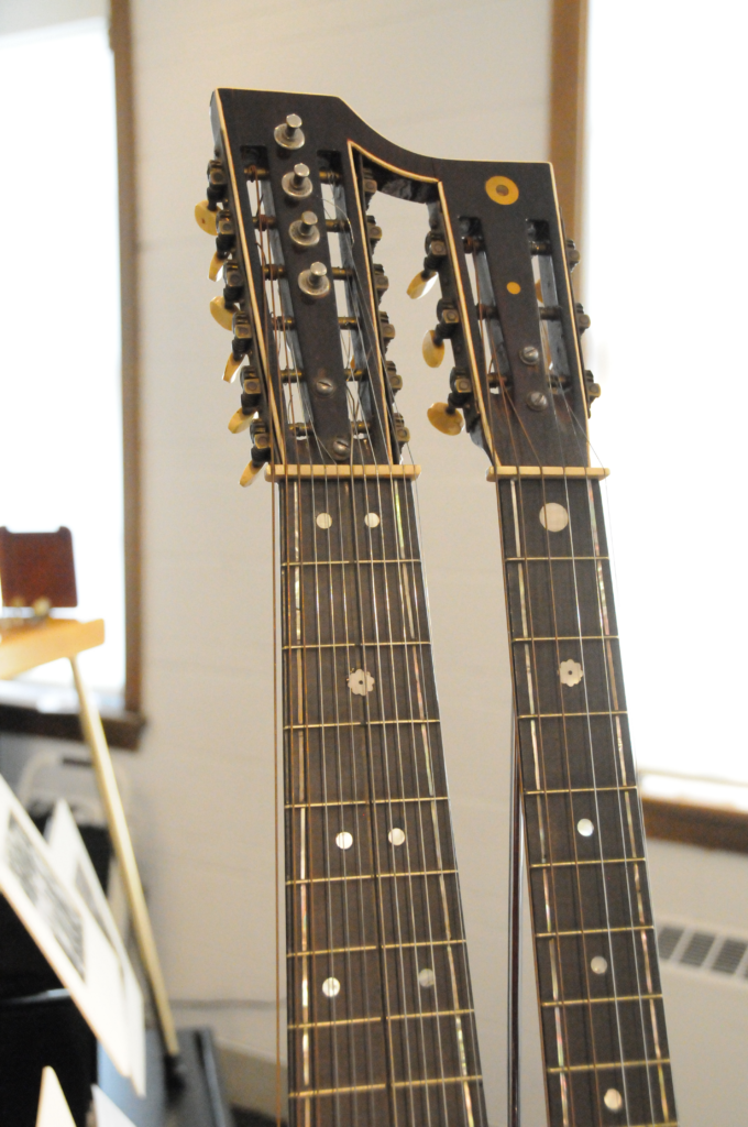 A close-up of the guitar's two necks, showing the fretboard.