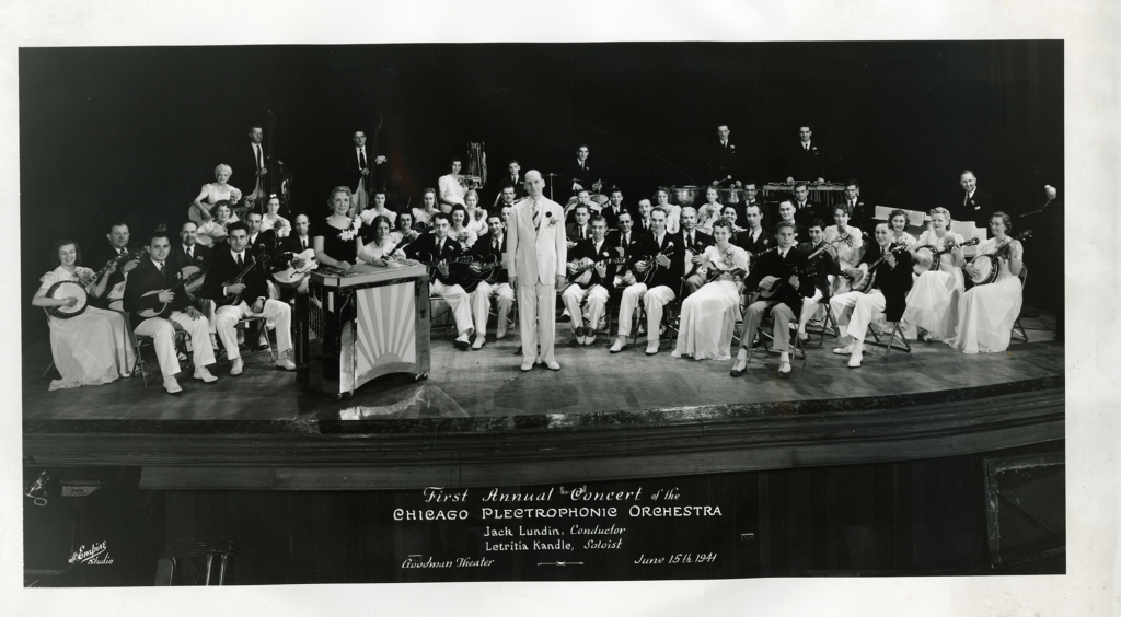 Kandle as a soloist with the Chicago Plectrophonic Orchestra, she is standing in front of the orchestra with the Grand Letar, next to conductor Jack Lundin.