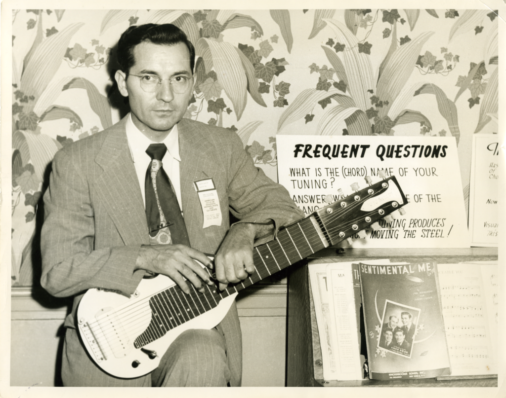 Eddie Alikre, sitting and holding a guitar, at the National Convention